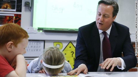 Britain's Prime Minister David Cameron reads a book to Lucy Howarth, 6, and Will Spibey, 5, during a visit to Sacred Heart RC primary school in Westhoughton on April 8, 2015 near Bolton, England.