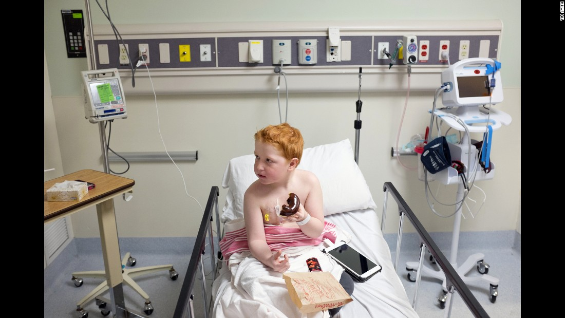 Mauthe's son, Colin, eats a doughnut in the emergency room in March 2014. He was diagnosed with leukemia in 2012, two years before his mother was diagnosed with breast cancer.
