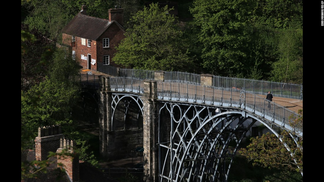 A man walks across the world's first-ever iron arched bridge toward a polling station in Ironbridge, England.