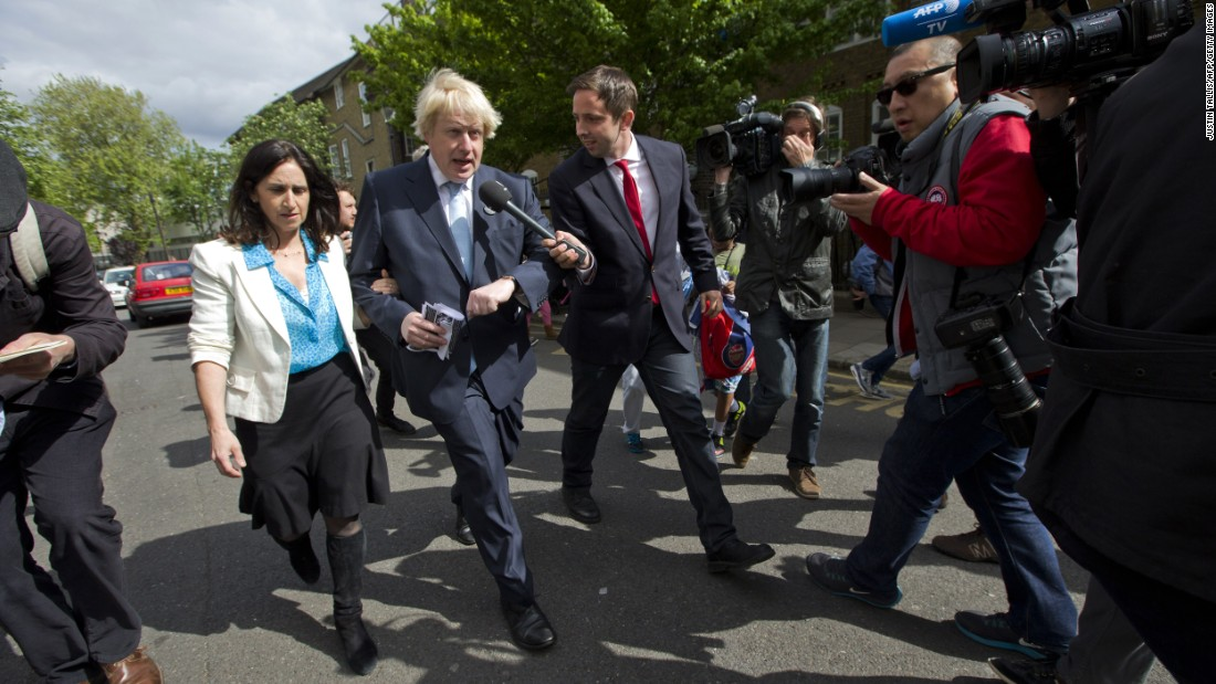 Members of the media follow London Mayor Boris Johnson and his wife, Marina Wheeler, after they voted in London.