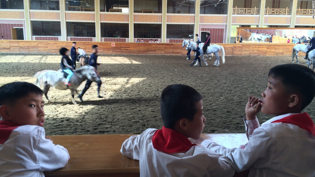 North Korean students watch horse riding lessons at a new equestrian center designed by Supreme Leader Kim Jong Un. The facility was formerly used for military training.