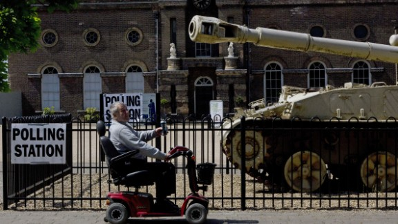 A man rides a mobility scooter past a an armored vehicle outside the polling station at the Greenwich Heritage Centre in London.