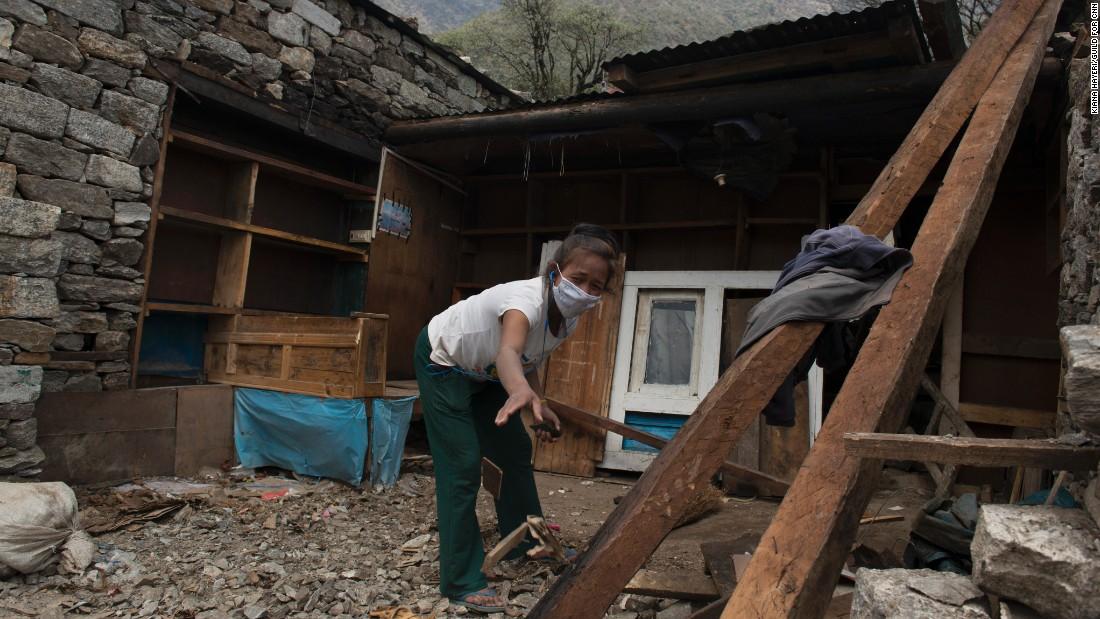 A girl helps clean out rubble from her family home in the village of Kyongma. In some villages, almost every house was damaged in the massive quake.