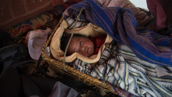 Nawang Sherpa held onto his baby girl during the earthquake. They survived but are now too frightened to sleep within cracked walls. The family of four lives in a tent set up nearby.