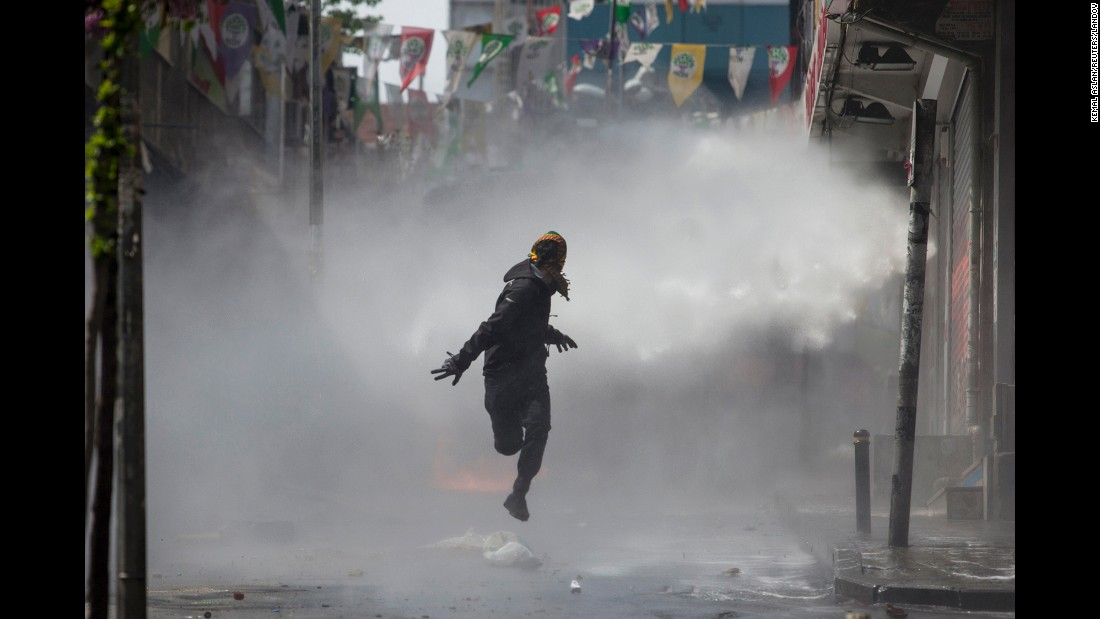 "A masked protester runs away from a police water cannon in Istanbul, Turkey, on Friday, May 1. Clashes erupted between police and protesters, who defied a government ban on marching to Taksim Square. <a href=""http://www.cnn.com/2015/05/01/world/gallery/may-day-pictures-2015/index.html"" target=""_blank"">Rallies around the world</a> marked May Day, referred to as International Workers' Day in many countries."