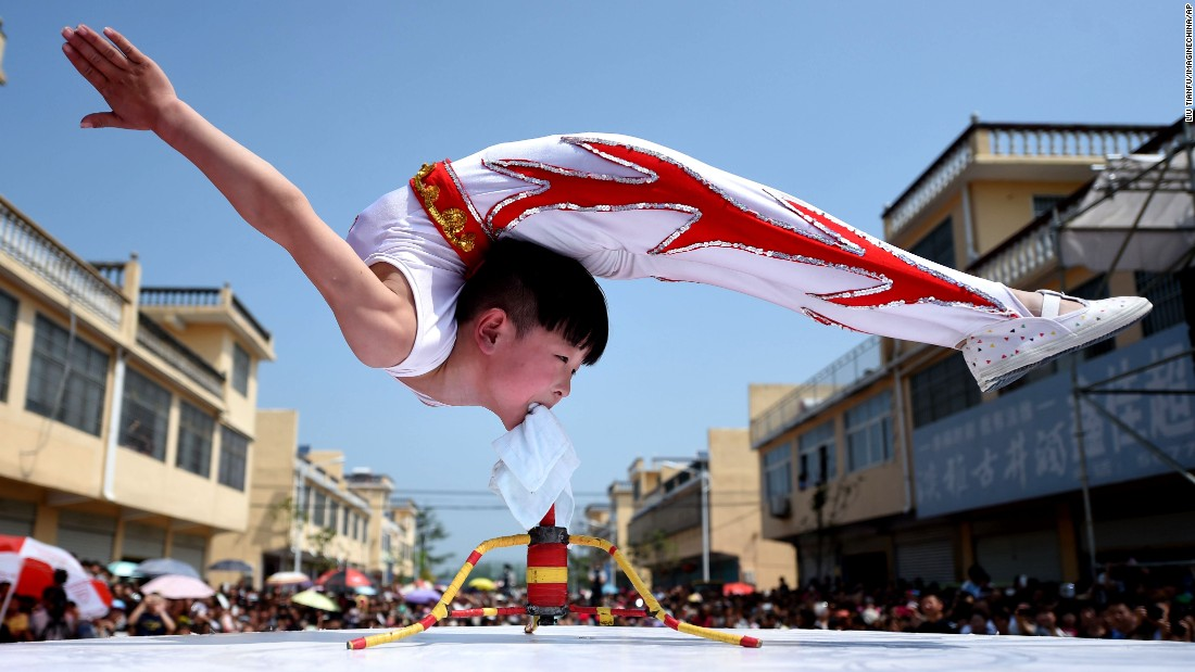 A 6-year-old acrobat balances with his mouth gripping a tripod during the opening ceremony of a tourism festival in Bozhou, China, on Sunday, May 3.