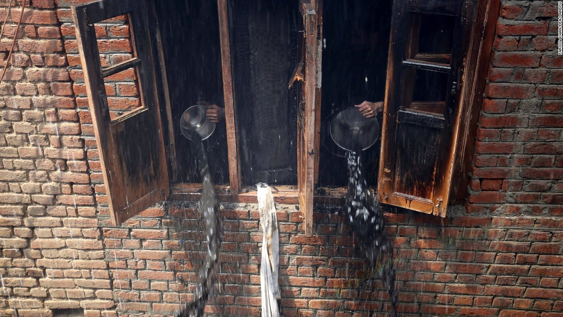 Kashmiri men dump out the water that had been used to douse flames during a blaze on Friday, May 1, in Srinagar, the summer capital of the Indian state of Kashmir. At least three residential houses were damaged in the fire but no casualties were reported.
