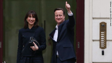Prime Minister David Cameron arrives in London with his wife Samantha