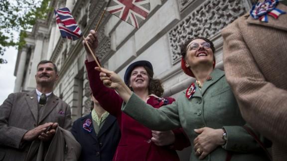 Spectators in London wave flags and wear World War II-era clothing.