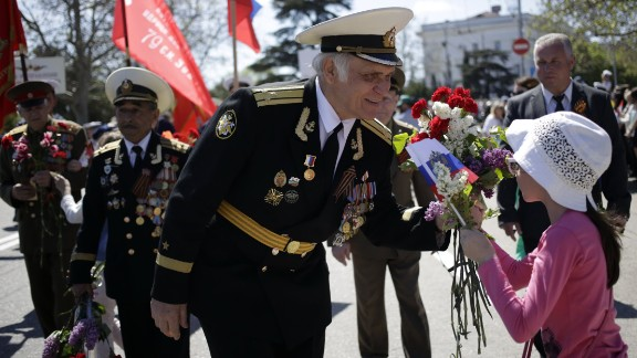 A Crimean veteran accepts flowers from a young girl during a march in central Sevastopol on May 9. Friction continues between Russia and Western nations that were allied with the former Soviet Union during World War II, stemming from Russia