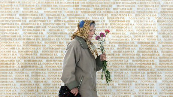 An elderly woman passes by a wall engraved with the names of the Soviet Union Heroes, during the 70th anniversary of the victory over Nazi Germany, in Ukraine