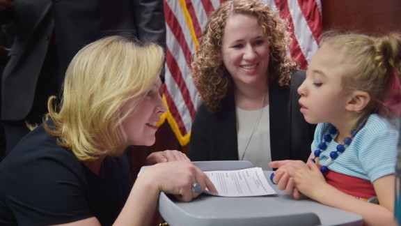 Senator Kirsten Gillibrand speaking with 4-year-old Morgan Hintz as her mother Kate Hintz looks on during a press conference to announce a new medical marijuana bill at the U.S. Capitol on March 10, 2014 in Washington, DC.