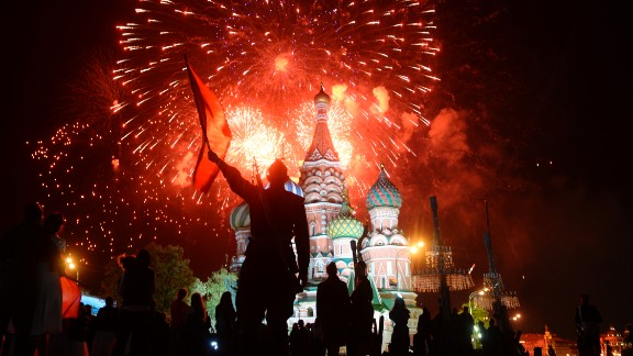 Actors dressed in World War II-era Soviet uniforms watch fireworks over St. Basil Cathedral in Moscow