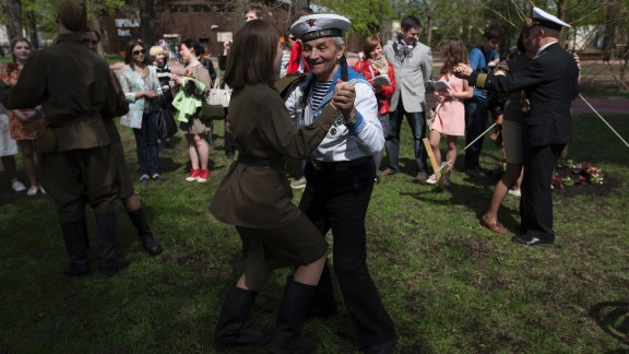 Victor Novopashin, a Russian World War II veteran, dances with a young woman dressed in Soviet-era uniform in Gorky Park in Moscow on May 9.