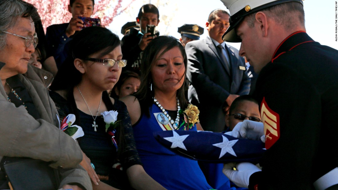 "Navajo Nation Police Officer Alex Kee Yazzie <a href=""https://www.odmp.org/officer/22418-police-officer-alex-yazzie"" target=""_blank"">was killed March 19</a> in a shootout with a suspect near the Arizona-New Mexico state line. Here, a member of the U.S. Marine Corps presents a American flag to his family during the burial service."