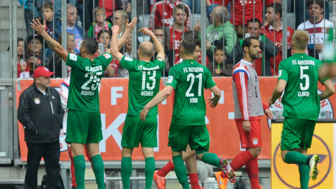 Augsburg players celebrate Raul Bobadilla's winning goal in front of their traveling fans. Their win keeps them on track to book a place in next season's Europa League.