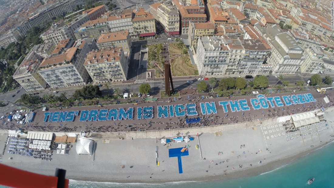 "Staff members lined up on the waterfront to spell out the phrase ""Tiens' dream is nice in the Côte d'Azur."""