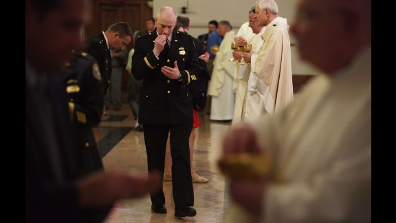 Police officers take communion during the Mass on May 5.