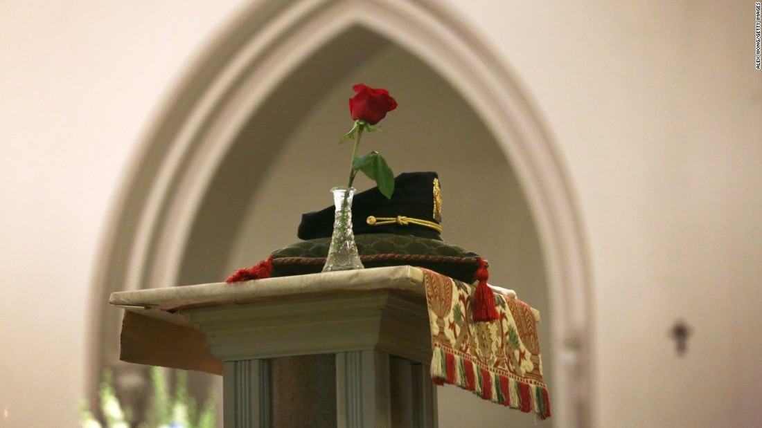 A police hat is placed on a column during the Mass.