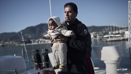An officer of Hellenic coast guard holds a baby as migrants arrive at the port of Lesbos island on April 30, 2015.