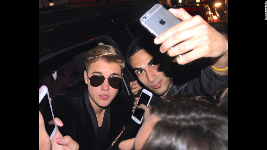 Pop star Justin Bieber sticks his head out a car window to pose for fan photos in New York on Thursday, May 7.