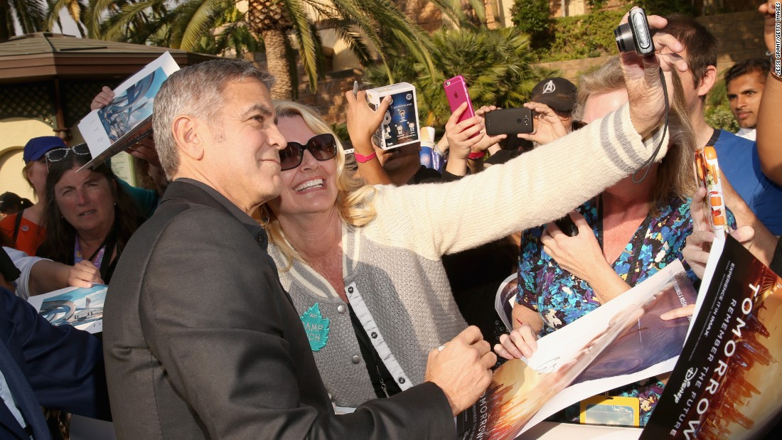 "Actor George Clooney smiles for a fan's selfie while attending the ""Tomorrowland"" premiere, which took place Saturday, May 9, in Anaheim, California."