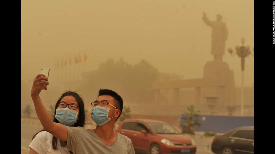 "A couple takes a selfie near a statue of Mao Zedong during a sandstorm in Kashgar, China, on Sunday, May 10. <a href=""http://www.cnn.com/2015/05/06/living/gallery/selfies-look-at-me-0506/index.html"" target=""_blank"">See 21 selfies from last week</a>"