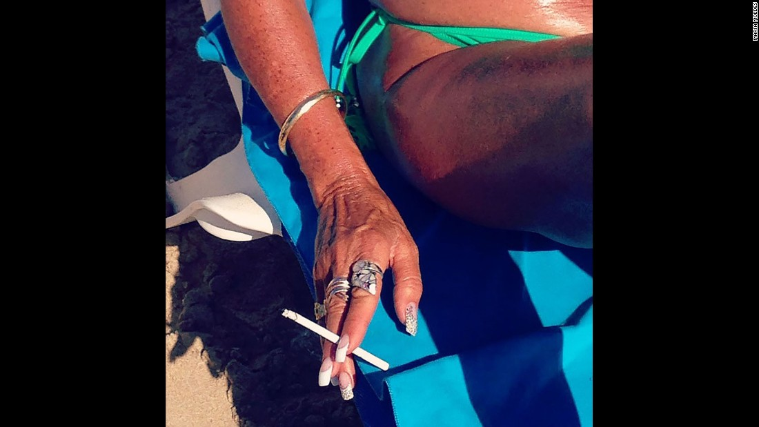 A woman smokes a cigarette on the beach.