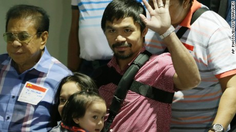 Filipino boxer Manny Pacquiao waves to the crowd upon arrival with his family including his wife Jinkee and youngest son Israel (bottom left) on May 13 at the airport in the Philippines.