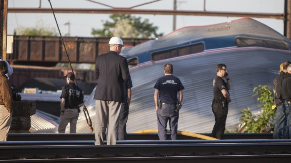 Rescue crews and investigators inspect the crash site on May 13. The impact of the crash tore cars apart, sending seven of them flying from the tracks. It also left the engine a mangled mess.