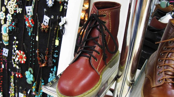"""In an air-conditioned, multi-level mall in Bangkok, a sign deceptively advertises """"Dr. Martens"""" next to boots resembling the real thing, but without any logos on the leather or soles."""