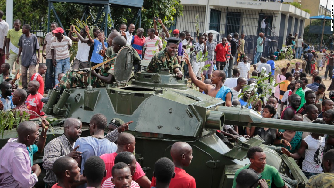 With army soldiers riding in an armored vehicle, demonstrators in Bujumbura celebrate the reported coup attempt on May 13.