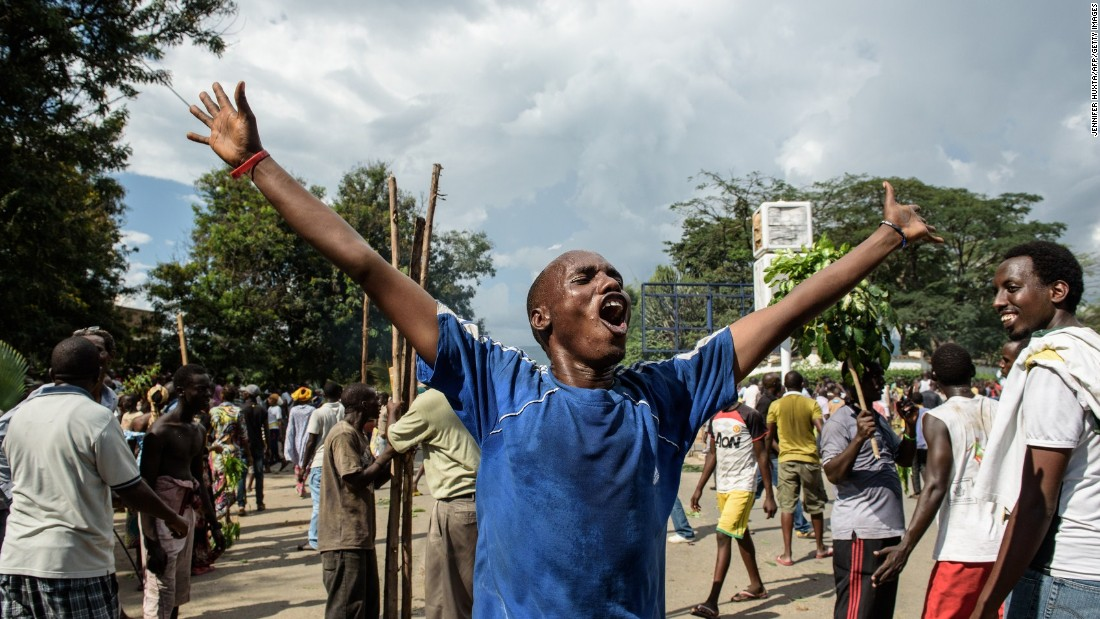 A man raises his arms as people celebrate in the streets of Bujumbura on May 13 after a radio announcement that Nkurunziza was overthrown.