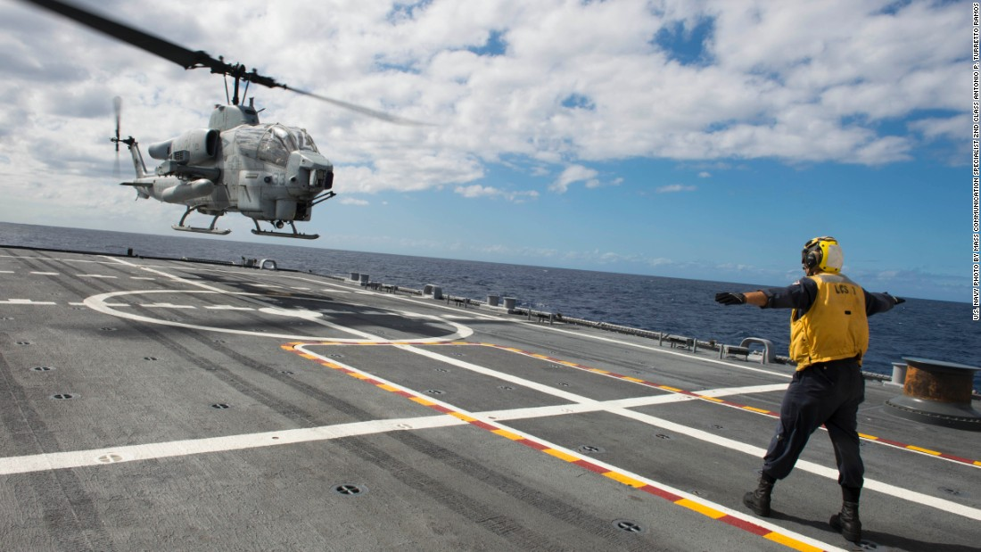 Boatswain's Mate 2nd Class Adam Garnett, from Anchorage, Alaska, signals an AH-1 Cobra helicopter from Marine Air Group (MAG) 24 during deck landing qualification training aboard the USS Fort Worth (LCS 3). The LCSs are designed to support air operations by both helicopters and helicopter drones.