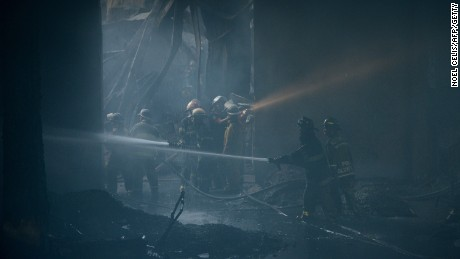 Firefighters tackling the fire that tore through a factory producing footwear in the Philippines on Wednesday.