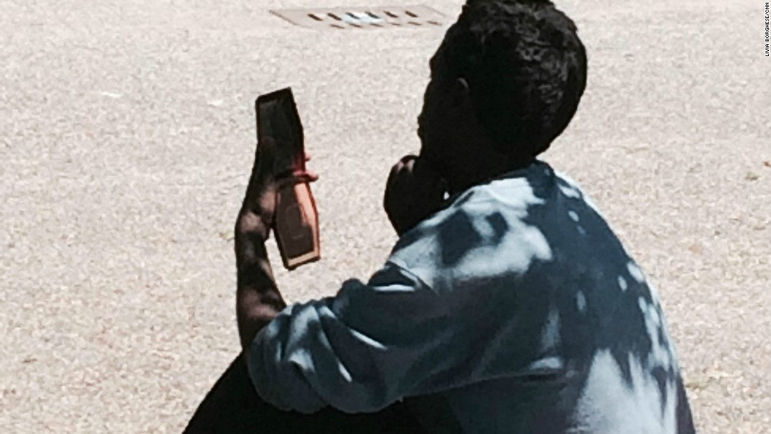 An Eritrean man stares at a cell phone. According to European Union regulations, migrants must be registered in the country they arrive in, and cannot go on to request asylum elsewhere. But many who arrive in Italy flee before they are registered hoping to make it to other European countries.