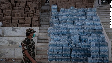 A soldier walks past a pile of water and aid packages at the temporary camp for earthquake evacuees at Tundikhel Park, Kathmandu.