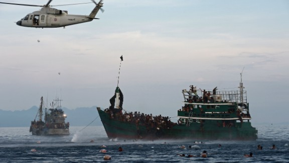 Rohingya migrants swim to collect food supplies dropped by a Thai army helicopter after they jumped from the boar adrift in Thai waters on May 14.  With the Thai pipeline for illegal migrants closed, overcrowded traffickers