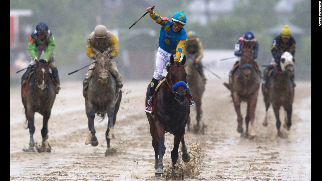 Victor Espinoza exults as he rides Kentucky Derby champ American Pharoah to victory at the Preakness.