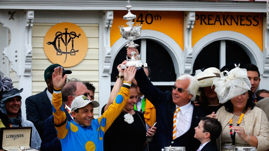 Jockey Victor Espinoza and trainer Bob Baffert celebrate in the winner's circle after American Pharoah won the 140th running of the Preakness Stakes at Pimlico Race Course on Saturday, May 16, in Baltimore, Maryland.