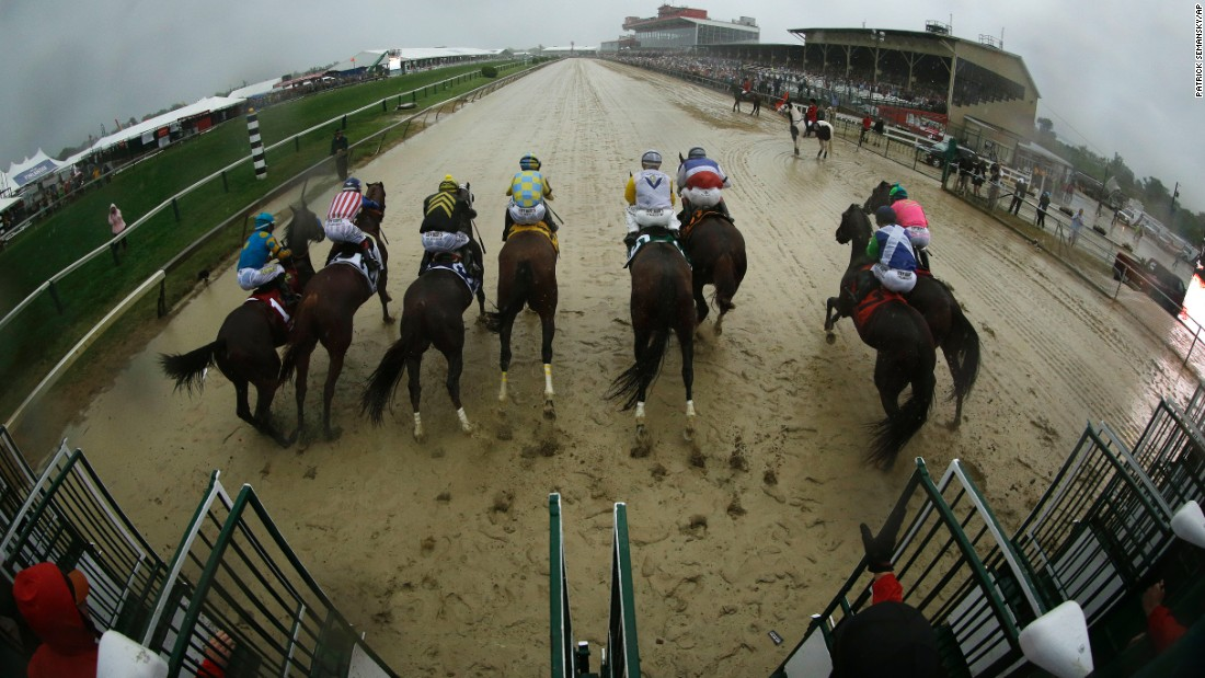 The horses leave the starting gate in the post-storm muck.