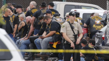A McLennan County deputy stands guard near a group of bikers in the parking near where the shooting took place.