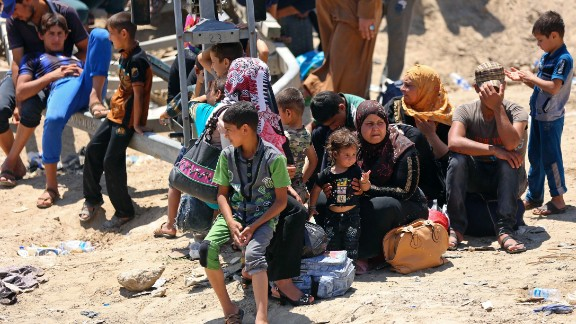 Displaced Iraqis from Ramadi rest before crossing the Bzebiz bridge after spending the night walking towards Baghdad, as they flee their hometown, 65 km west of Baghdad, Iraq, Saturday, May 16, 2015. Islamic State militants seized the center of Ramadi in western Iraq and raised their black flag over the government compound, local officials said.