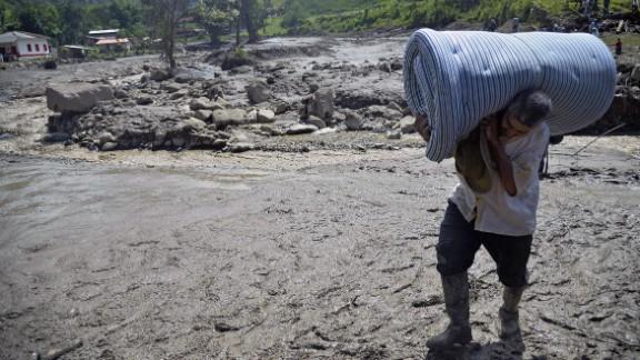 A man carries a mattress after the landslide.