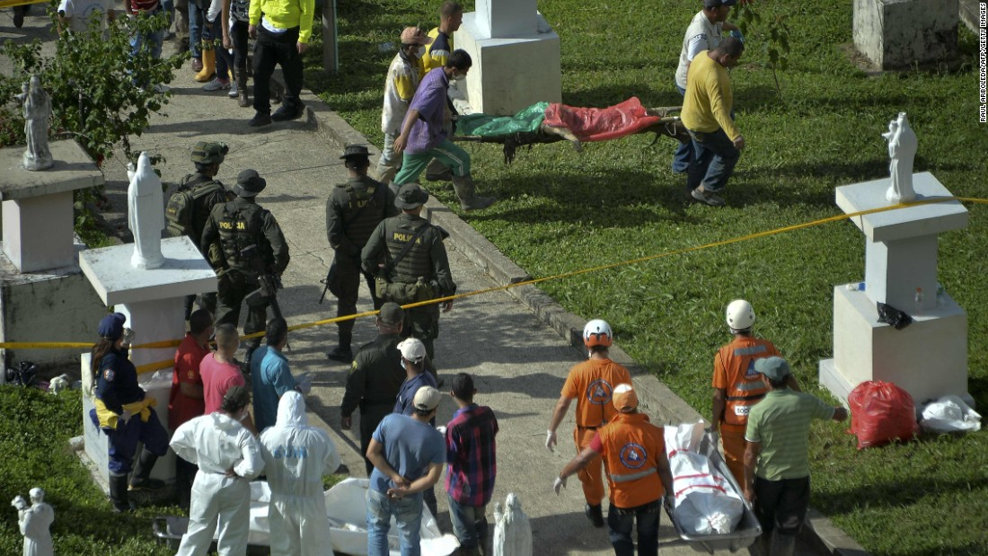 Rescue workers carry corpses after the disaster.