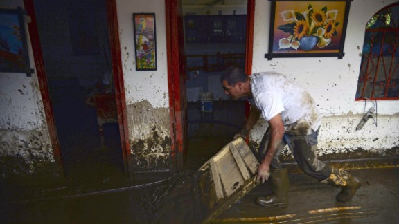A man cleans his house after the landslide.