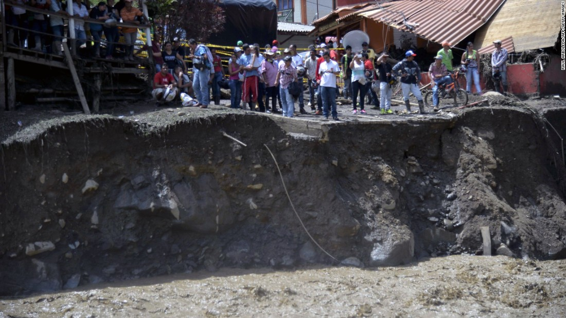 People stand near the site of a massive landslide in Salgar, Colombia, on Monday, May 18. The landslide tore through a ravine before dawn, killing more than 80 people, officials said.