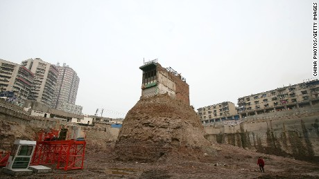 A building sits on its own island of land amid construction all around March 21, 2007 in Chongqing Municipality, China. The homeowner, who has hung a banner and the national flag in protest, has refused to sell to a developer who went ahead with construction around the site. The Jiulongpo District Court has ordered the household to move out before March 22. The National People's Congress, China's legislature, just approved a much-debated new property law that for the first itme provides legal protections for private assets in China.