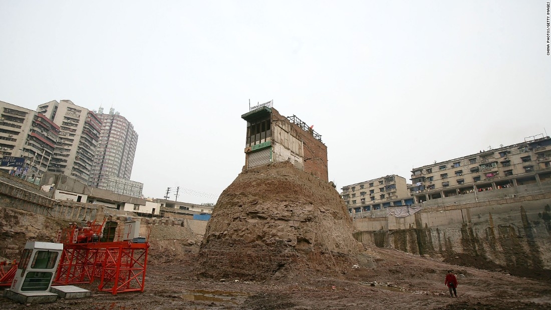 "One of the most famous ""nail houses"" was a building in Chongqing, western China. The homeowner hung a banner and the national flag in protest and refused to sell to a developer who went ahead with construction around the site in 2007."