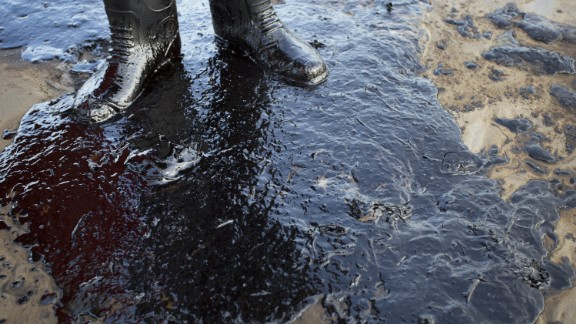 Oil surrounds the feet of local resident Morgan Miller as he patrols the beach for affected wildlife on Tuesday, May 19.